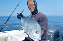Thomas is very happy catching this GT or giant trevally fish